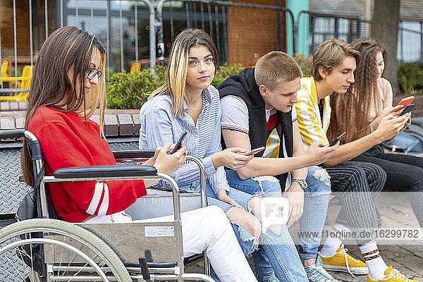 Junge Frau mit Freunden  die im Freien sitzend ihre Smartphones benutzen