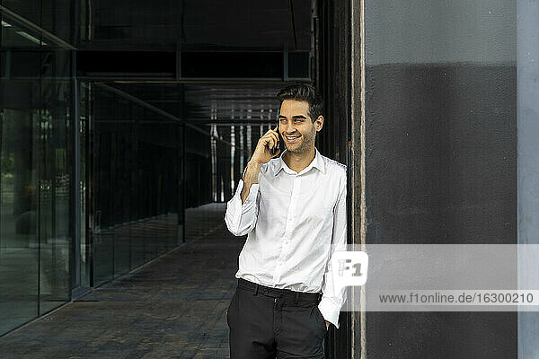 Smiling male professional talking over smart phone while standing in office