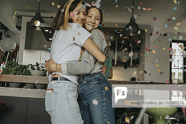 Loving teenage friends embracing while standing in birthday party at home