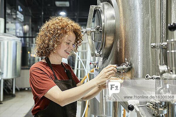 Frau arbeitet in einer Handwerksbrauerei und zapft Bier aus einem Tank Frau arbeitet in einer Handwerksbrauerei und zapft Bier aus einem Tank