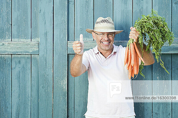 Germany  Bavaria  Man in front of barn door holding bunch of carrots  smiling  portrait