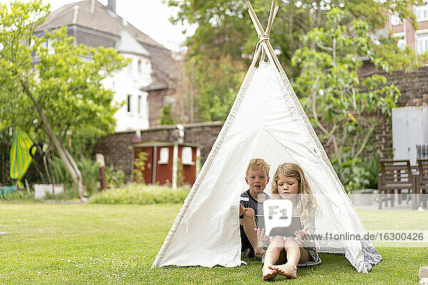Cute siblings with digital tablet sitting in tent on grass at back yard during weekend
