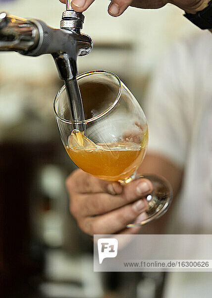 Close-up of barkeeper tapping beer
