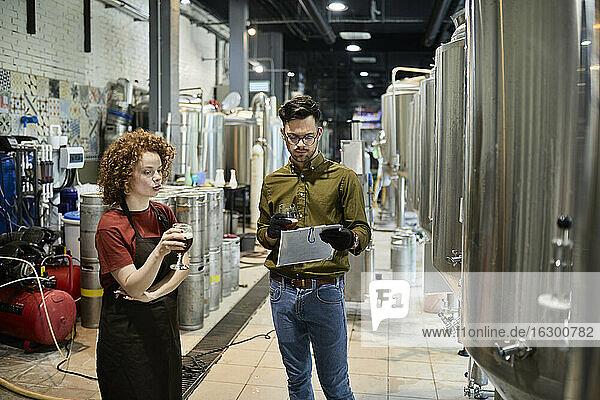 Ein Mann und eine Frau arbeiten in einer handwerklichen Brauerei und diskutieren über die Qualität eines Bieres