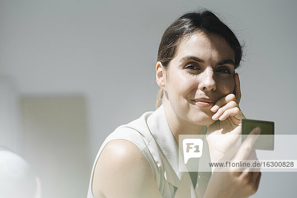 Woman holding businness card at office