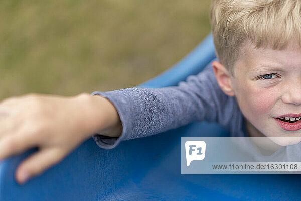 Blond boy lying on blue slide at back yard