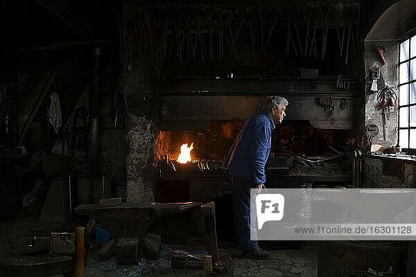 Germany  Bavaria  Josefsthal  blacksmith with glowing pickaroon at historic blacksmith's shop