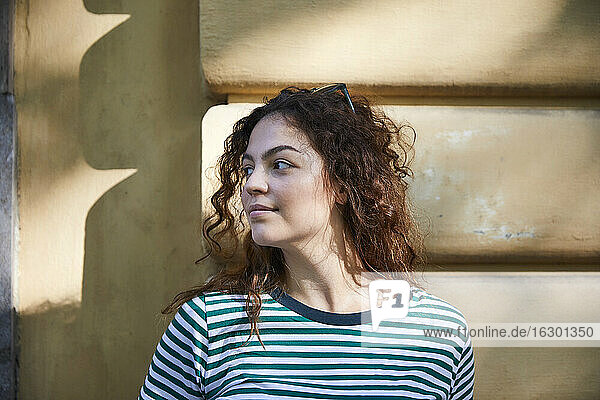 Portrait of brunette woman looking sideways in front of wall