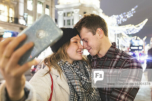 Close-up of romantic couple with face to face taking selfie in city at night