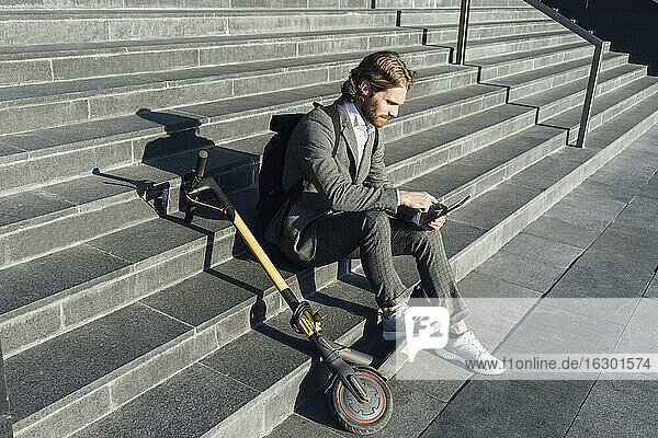 Young businessman with digital tablet and electric push scooter sitting on steps at downtown during sunny day