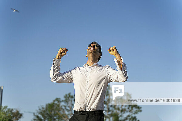 Excited businessman gesturing while standing against clear blue sky