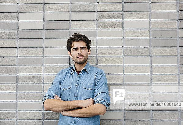 Gutaussehender Geschäftsmann mit verschränkten Armen  der an einer Backsteinmauer steht Gutaussehender Geschäftsmann mit verschränkten Armen, der an einer Backsteinmauer steht