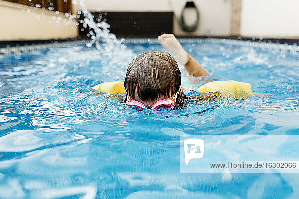 Little girl diving in swimming pool