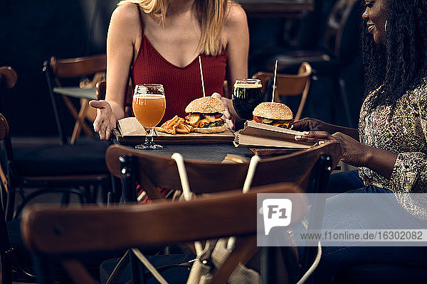 Weibliche Freunde essen einen Burger in einer Kneipe Weibliche Freunde essen einen Burger in einer Kneipe