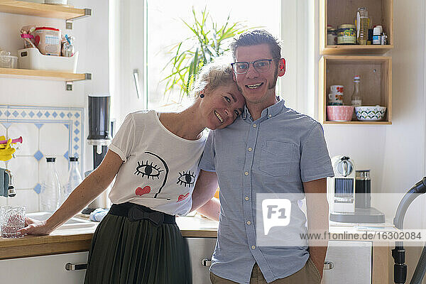 Smiling woman leaning on man's shoulder while standing in kitchen