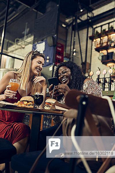 Glückliche Freundinnen mit Smartphone beim Burgeressen in einer Kneipe Glückliche Freundinnen mit Smartphone beim Burgeressen in einer Kneipe