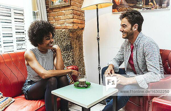 Fröhliches Paar mit Kaffee auf dem Tisch  das sich in einem Café unterhält