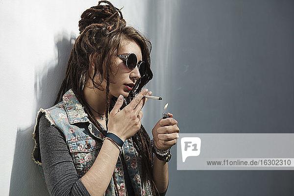 Rastafarian woman lighting cigarette against wall