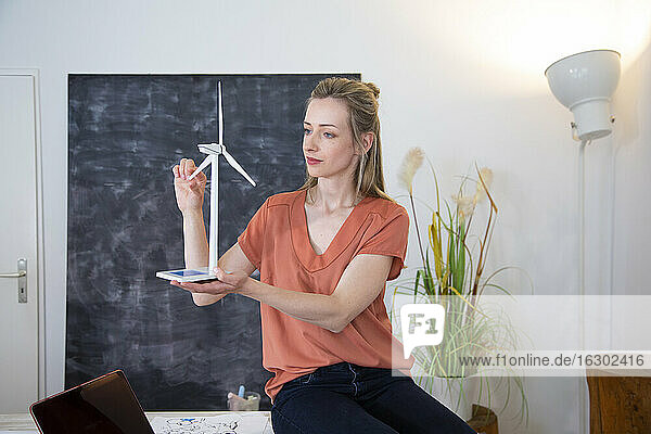 Woman in office holding wind turbine model