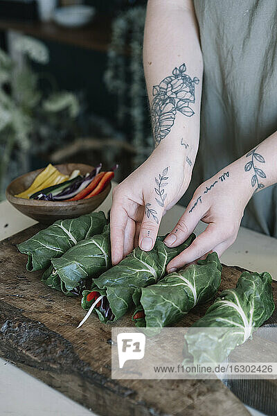 Young woman preparing vegan rolls with vegetables