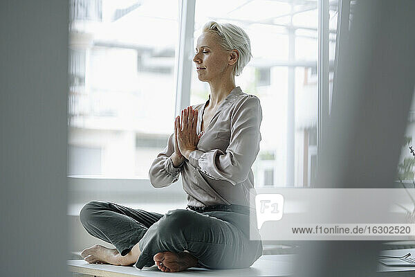 Businesswoman with eyes closed meditating while sitting against window in loft office