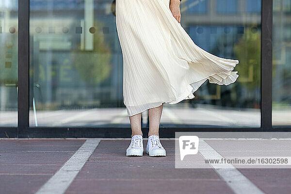 Legs of senior woman standing against glass window on footpath
