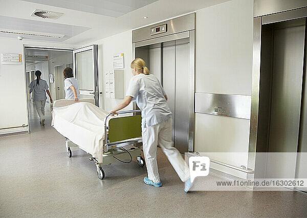 Deutschland  Freiburg  Krankenschwestern bewegen Krankenhausbett