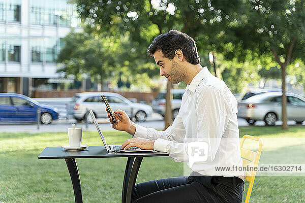 Businessman using mobile phone and laptop while sitting at sidewalk cafe