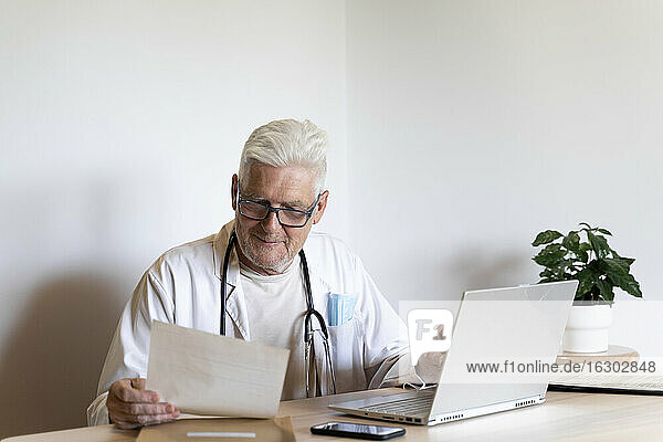 Smiling doctor looking at medical record while sitting against wall
