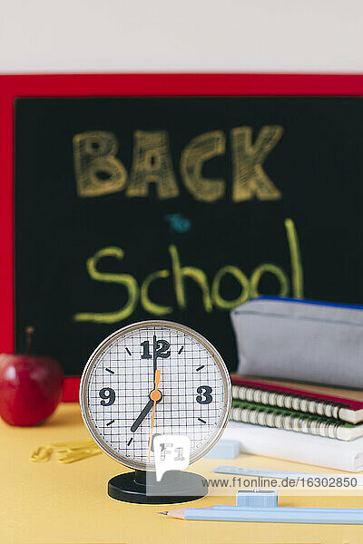 Close-up of alarm clock against school supplies on table