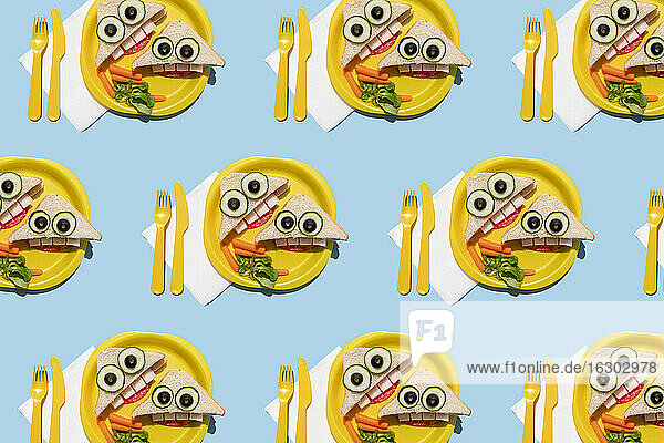 Pattern of plastic plates with funny looking sandwiches withanthropomorphic faces