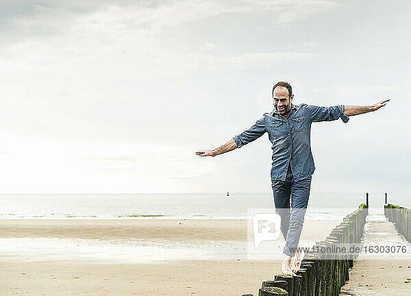 Carefree man with arms outstretched walking on wooden post at beach