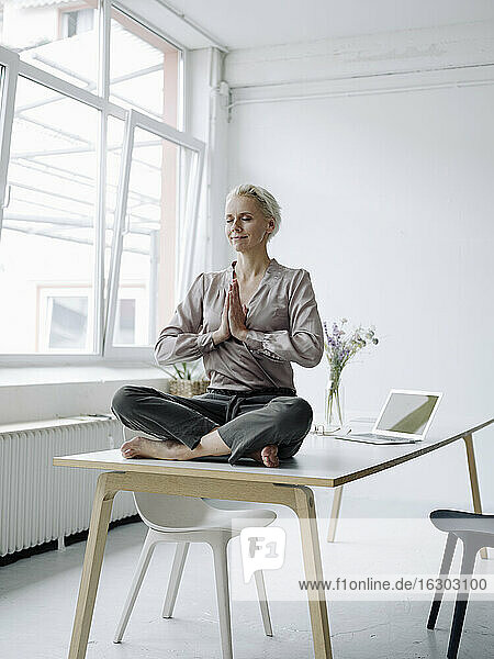 Businesswoman meditating while sitting on desk in loft office
