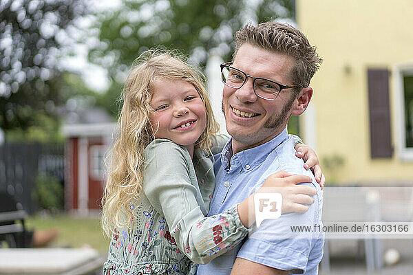 Lächelnder Mann mit blonder Tochter im Hinterhof