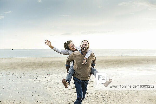 Happy mature man piggybacking woman while walking at beach against cloudy sky