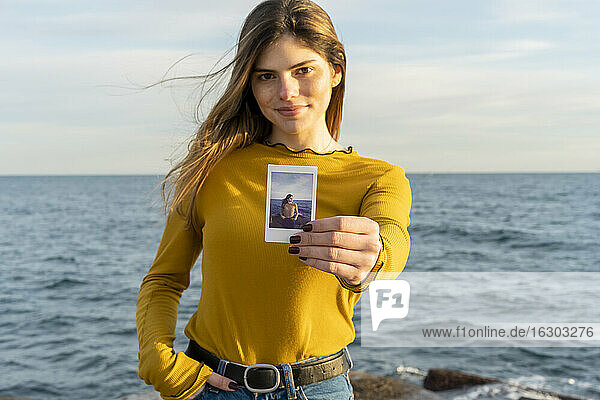 Smiling woman showing photograph while standing against sea