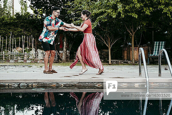Man and women dancing by poolside
