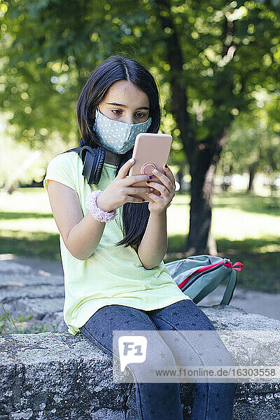 Girl with face mask using phone in public park
