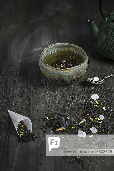 Japanese tea pot and bowl with tea leaves on wooden table  studio shot