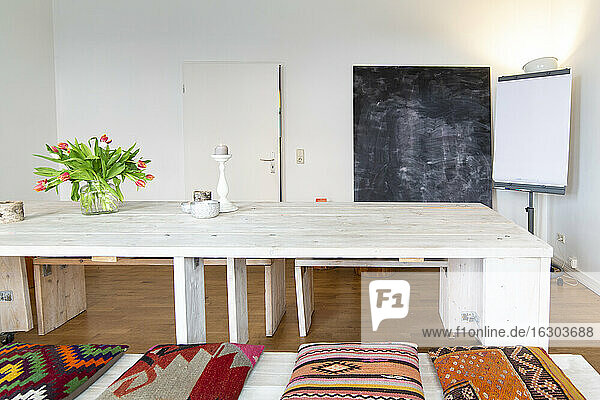 Room with wooden table  chalkboard and projection screen
