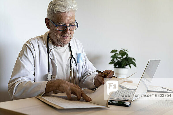 Senior doctor looking at medical record while sitting in clinic