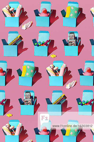 Pattern of boxes with various gifts including harmonicas  plastic spheres  vintage robot toys  sweets  rubber ducks and socks