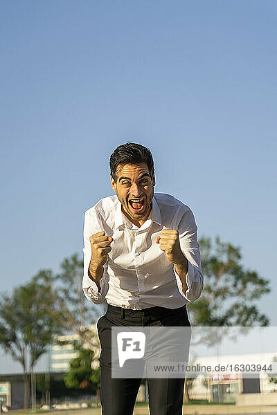 Successful businessman screaming while gesturing against clear blue sky