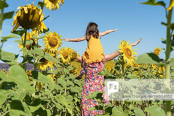Mother carrying daughter on shoulders in sunflower field against clear sky