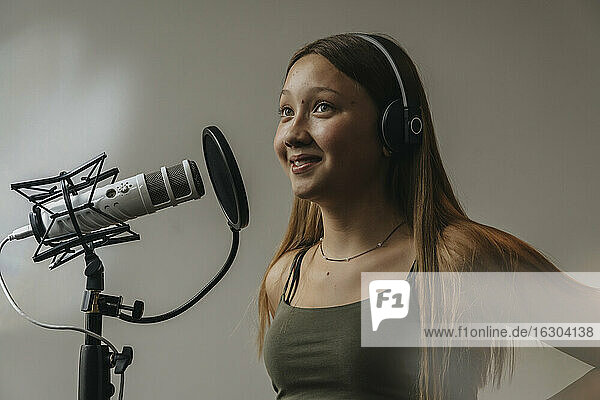 Close-up of smiling teenage girl singing over microphone against wall in recording studio