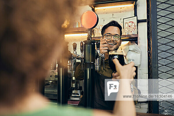 Barkeeper  der einer Frau in einer Kneipe ein Glas Bier überreicht Barkeeper, der einer Frau in einer Kneipe ein Glas Bier überreicht