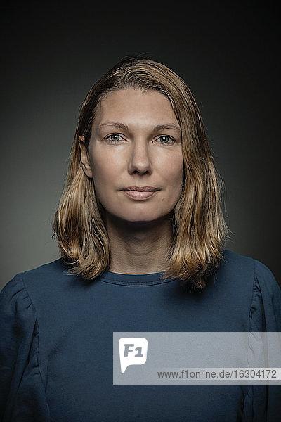 Frau mit blondem Haar stehend vor grauem Hintergrund