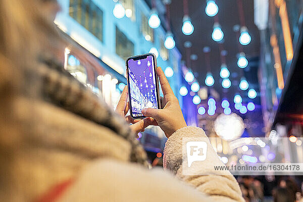 Close-up of woman photographing illuminated Christmas lights in city at night