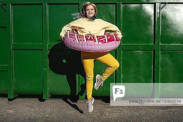 Young woman with dyed hair and floating tyre dancing in front of green container
