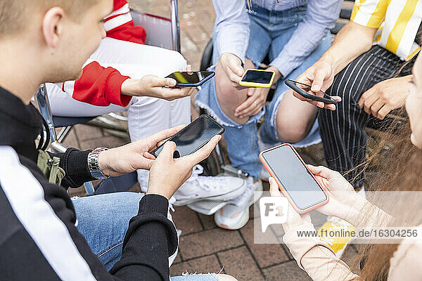 Friends using smart phones while spending leisure time together